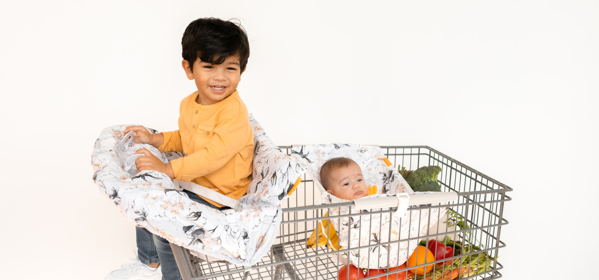 baby in floral shopping cart hammock