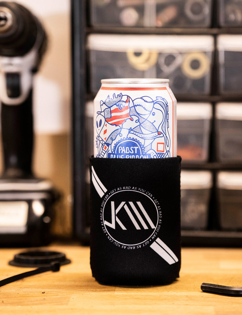 Jeff Kendall-Weed branded beer can koozie in black and white.
