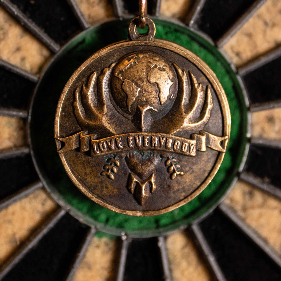 Primary Love Everybody pendant design hovered over the bullseye of a dartboard