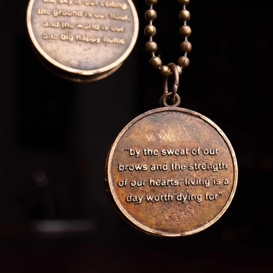 Closeup of medallion inscribed with inspirational phrase, side B