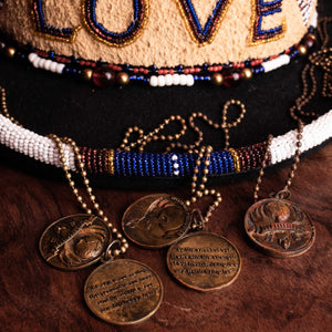 Necklaces draped across the brim of Big Kenny's Love top hat