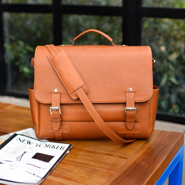 Gaston full-grain brown leather messenger bag on a table with the New Yorker