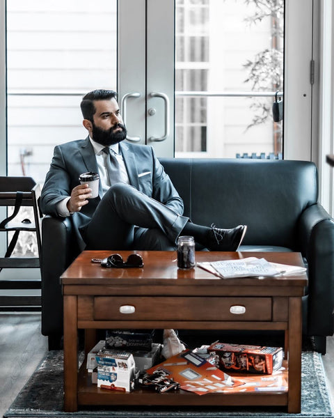 young man with beard sitting on a couch in a suit