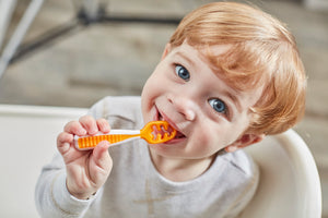 self-feeding baby spoon being used by a happy baby