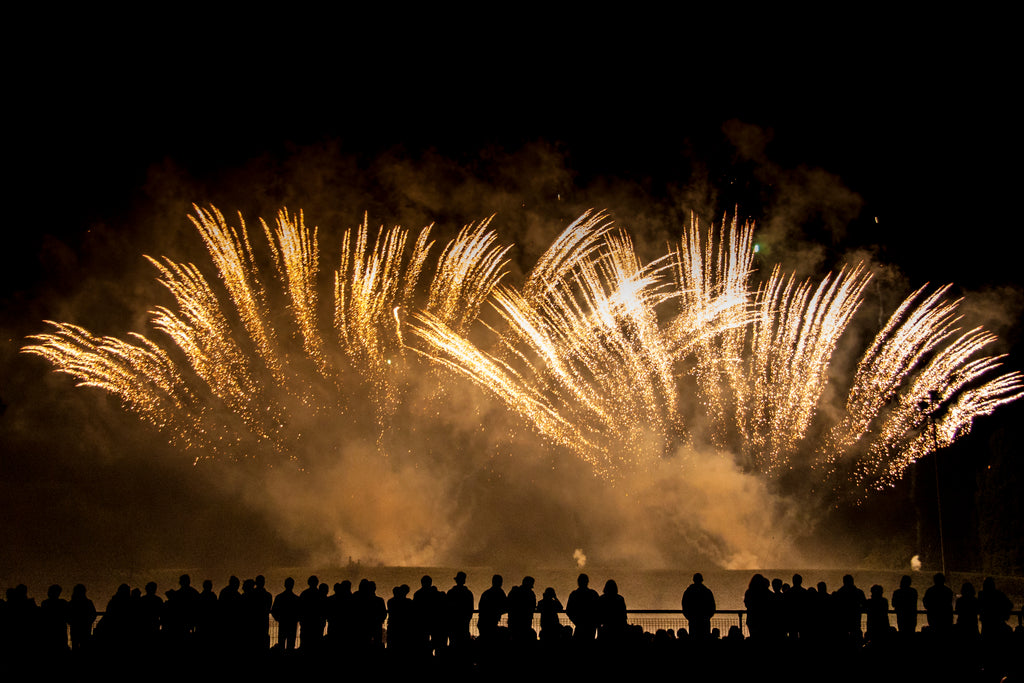 Golden pyrotechnics and fireworks exploding in front of a silhouetted crowd