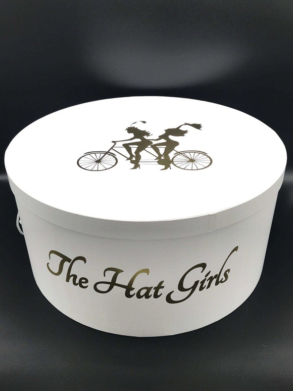 round, white hat box with gold brand logo