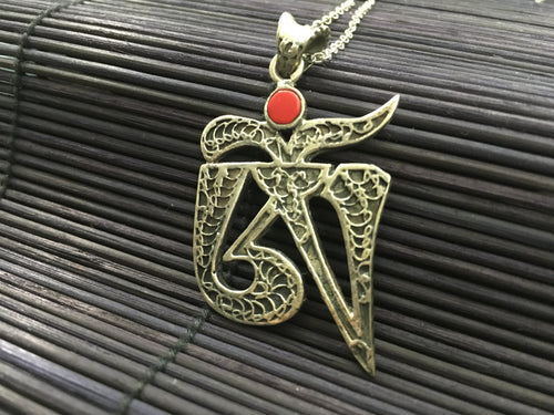 OM shaped silver pendant with red coral