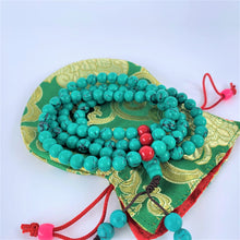 Load image into Gallery viewer, prayer beads mala turquoise coiled on bag