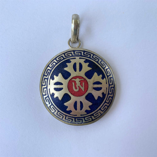 pendant double dorje on blue with OM syllable close up
