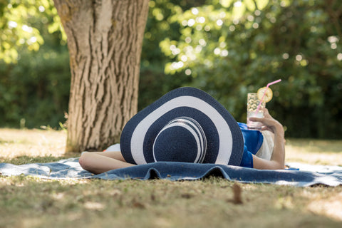 Woman in floppy hat laying in the shade with a drink