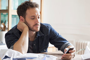 man not focused on work and texting on phone