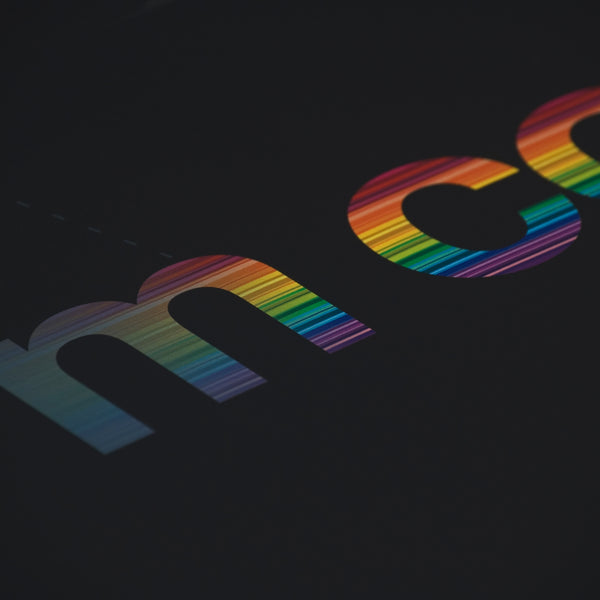 Close up detail of rainbow colours running through words on a typographic print