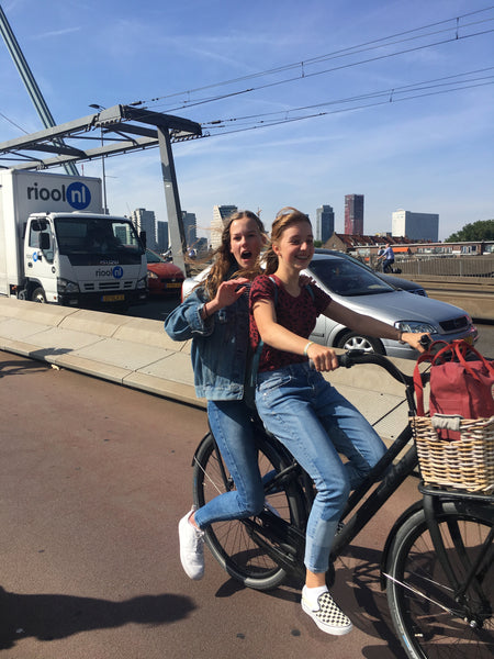 Happy Dutch girls riding their bikes over the Rotterdam bridge, photo by Susan Stokhof
