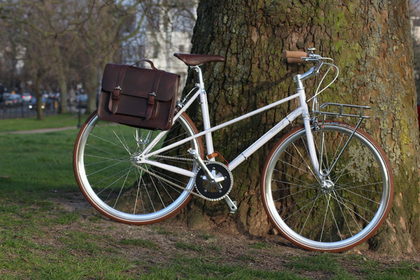 Hill and Ellis Fredie Classic Dark Brown Satchel on a white bicycle
