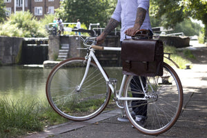 Bunbury Classic dark brown Leather Satchel on a white bicycle with model standing by