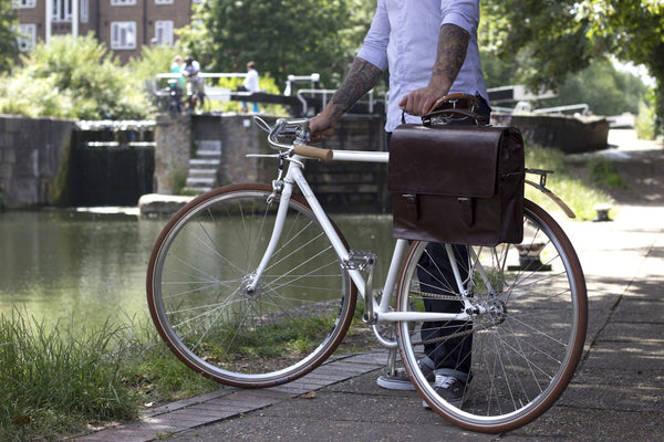 Hill and Ellis Bunbury Classic dark brown Leather Satchel on a white bicycle with model standing by