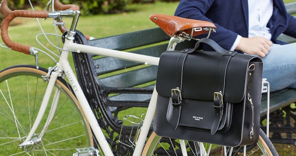 Hill and Ellis Byron Black Leather Pannier on a bicycle with model sitting on a bench beside the bicycle