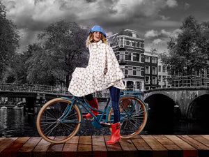 Image of model wearing HappyRainyDays rain cape while riding a bicycle
