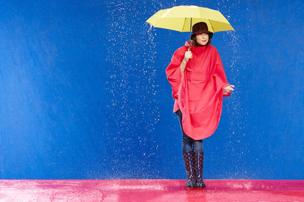 Photo of Model wearing a HappyRainyDays Rain Cape holding an umbrella
