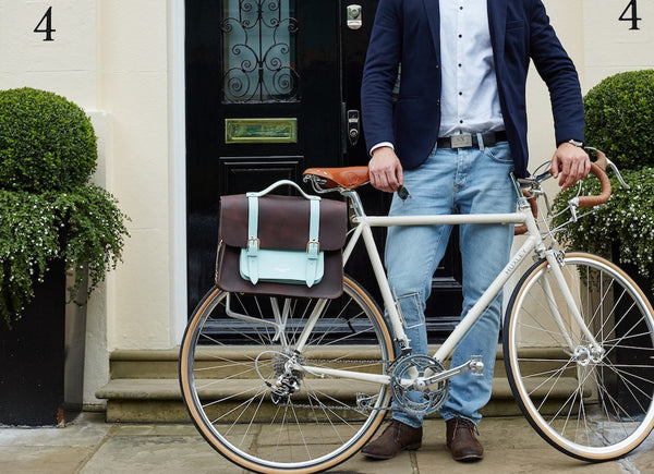 Don Dark Brown and Cambridge Blue Leather Pannier with male model holding up a bicycle that is holding the pannier