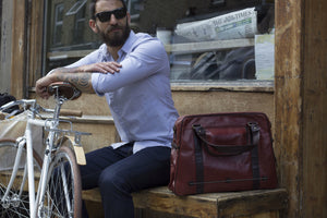 Hill and Ellis Duke Cherry Red Leather Satchel with model sitting on a bench beside a bicycle