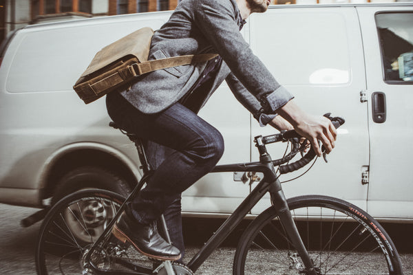 Male riding a bicycle wearing DU/ER jeans