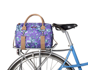 Po Campo Logan Trunk Bag in purple petals attached to the back of a bicycle