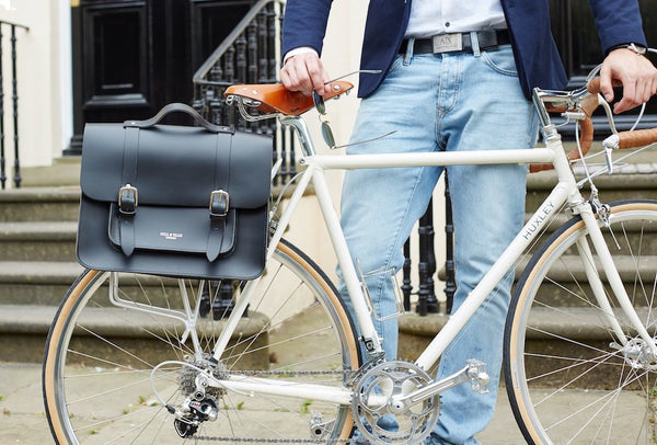Hill and Ellis Byron Classic Black Leather Pannier view of man holding up a bicycle, the Byron is attached to the bike