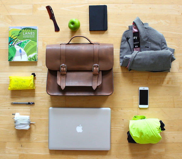 Hill and Ellis Mac Whiskey Tan Leather Pannier shown with items you can place inside like a laptop, phone, book, jacket etc.