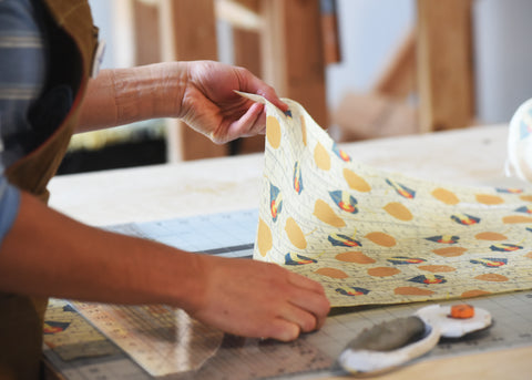 The process of cutting out a Khala & CO sustainable beeswax wrap, showing the production floor and a workers hands holding a sustainable beeswax wrap with the print Khalarado. This print has falling golden and colorado flag aspen leaves on a background of aspen bark and the Khala & CO logo.