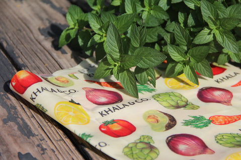 Clippings of mint atop a eco-friendly beeswax wrap in the print Harvest, which has realistically rendered ripe vegetables cascading down the fabric accompanied by the Khala & CO logo, on a wooden picnic bench drenched in sunlight.