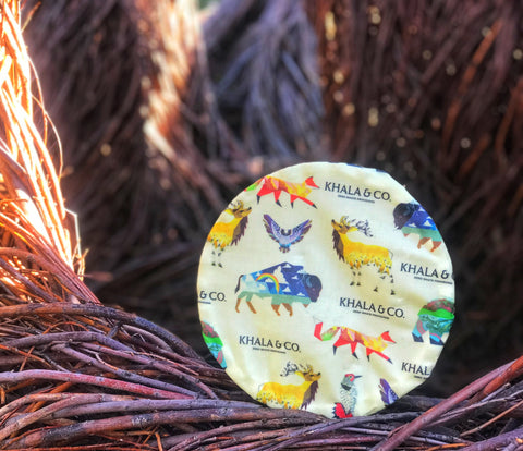 Bowl covered with an eco-friendly Khala & CO beeswax wrap on a round structure of ruddy red branches, featuring the print Windows into the Still Wild, which has various native Colorado Wildlife rendered in a colorful and abstract style.