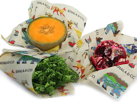 Produce in various states of cover by sustainable beeswax wraps, wrapped around cut edges of fruit or folded into bags to hold leafy greens. Print on all eco-friendly beeswax wraps is Window into the Still Wilds, featuring various native Colorado wildlife in an abstract style along with the Khala & CO logo.