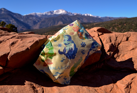 An ecofriendly beeswax wrap in the print Watershed Mermaids atop a red sandstone rock perched on a valley overlook. Watershed Mermaids is a colorufl print with mermaids representing three different ecosystems, with scattered shells and wave patterns throughout.