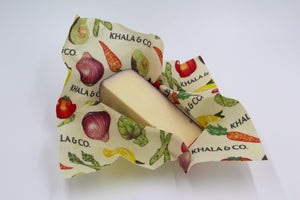 Beeswax Wrap Medium size wrapped around a cheese with purple rind, featuring the print Windows into the Still Wild. An eco-friendly way to cover your food, this wrap is re-usable, durable, and long lived! Windows into the Still Wild has a myriad of Colorado wildlife, including buffalo, bears, deer, foxes, owls, and northern flickers, all in a colorful and abstract styling.