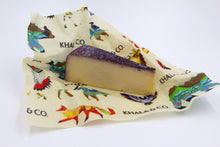 Load image into Gallery viewer, Beeswax Wrap Medium size enclosing a cheese with purple rind, featuring the print Windows into the Still Wild. An eco-friendly way to cover your food, this wrap is re-usable, durable, and long lived! Windows into the Still Wild has a myriad of Colorado wildlife, including buffalo, bears, deer, foxes, owls, and northern flickers, all in a colorful and abstract styling.