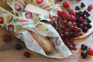 Eco-friendly Beeswax wrap Bread & Cheese bundle in action, enclosing a crusty baguette and cheese surrounded by fresh fruit on a wooden table. Eco-friendly alternative to plastic wrap, durable, re-usable, and long lived, these wraps are great for those living a Zero Waste lifestyle!
