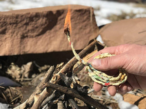 Eco-friendly Mechak rope in action, brightly lit and burning over the start of a campfire in the snow.