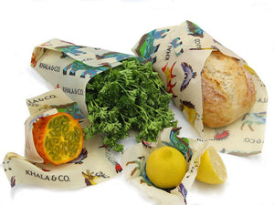 A sustainable Beeswax combo pack in action, the Large wrapped around a loaf of bread, a Medium wrapped around fresh leafy greens, the Small around half of a tropical fruit, and the Mini around a lemon half. All wraps feature Windows into the Still Wild, a print featuring many different Colorado animals. Beeswax wraps are an excellent alternative to plastic wrap, as they are durable, long lived, and re-usable, helping you live a Zero Waste lifestyle!