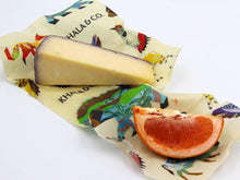 Load image into Gallery viewer, A 2 Mini 2 Small pack in action, the Small encasing a wedge of cheese and the mini containing a slice of blood orange. Both wraps have the print Windows into the Still Wild, a print featuring different Colorado animals. Beeswax wraps are a great alternative to plastic wrap, as they are re-usable, durable, and long lived, reducing the amount of plastic waste produced and helping you live a Zero Waste lifestyle.