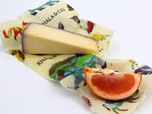 A 2 Mini 2 Small pack in action, the Small encasing a wedge of cheese and the mini containing a slice of blood orange. Both wraps have the print Windows into the Still Wild, a print featuring different Colorado animals. Beeswax wraps are a great alternative to plastic wrap, as they are re-usable, durable, and long lived, reducing the amount of plastic waste produced and helping you live a Zero Waste lifestyle.