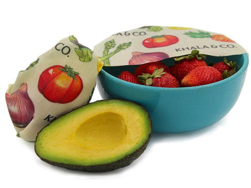 A sustainable Beeswax 2 Mini 2 Small pack in action, covering a bowl of vibrant ripe strawberries and wrapped around the cut side of a bright green avocado, perfectly replacing plastic wrap and eliminating the need for a plastic bag. Beeswax wraps are an excellent substitute for single-use alternatives, helping you live a Zero Waste lifestyle.