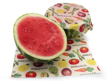 Load image into Gallery viewer, Beeswax 2 Large wraps in action, covering the cut sides of half a watermelon. Features the print Harvest, which has various vegetables cascading down the fabric and the Khala & CO logo. Beeswax Wraps are an excellent alternative to plastic wrap, and are both more durable and longer lasting (upwards of a year) than plastic alternatives. Wonderful for anyone trying to find more re-usable products and live a Zero Waste life.