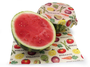 Beeswax 2 Large wraps in action, covering the cut sides of half a watermelon. Features the print Harvest, which has various vegetables cascading down the fabric and the Khala & CO logo. Beeswax Wraps are an excellent alternative to plastic wrap, and are both more durable and longer lasting (upwards of a year) than plastic alternatives. Wonderful for anyone trying to find more re-usable products and live a Zero Waste life.