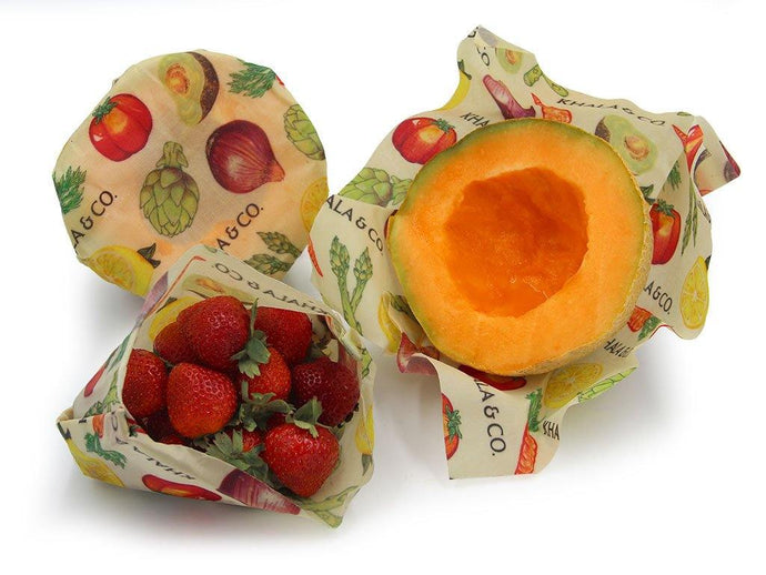 Sustainable Vegan Wax wrap 3 Medium pack in action, covering the cut sides of ripe canteloupe and folded into a bag to enclose delicious ruby red strawberries as an eco-friendly alternative to plastic wrap or bags. All wraps are in the print Harvest, which has bright and ripe vegetables painted in a realistic style, showcasing lemons, carrots, avocadoes, tomatoes, onions, artichokes, and asparagus.