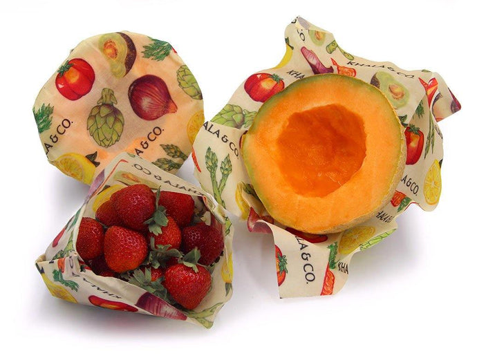Medium sized beeswax Khala Cloths folded into a bag to hold strawberries and wrapped around the cut half of a melon. Cloths are in the print Harvest