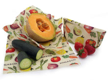 Load image into Gallery viewer, Sustainable Beeswax Wraps in various sizes wrapped around fresh produce or folded into bags to replace plastic wrap or plastic bags, as a re-usable and sustainable alternative. All wraps feature the print Harvest, which has bright and ripe vegetables painted in a realistic style, showcasing lemons, carrots, avocadoes, tomatoes, onions, artichokes, and asparagus.