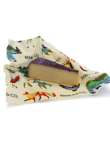 Beeswax Wrap Medium size enclosing a cheese with purple rind, featuring the print Windows into the Still Wild. An eco-friendly way to cover your food, this wrap is re-usable, durable, and long lived! Windows into the Still Wild has a myriad of Colorado wildlife, including buffalo, bears, deer, foxes, owls, and northern flickers, all in a colorful and abstract styling.