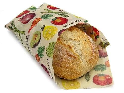 Eco-friendly Beeswax Potluck Wrap surrounding a crusty loaf of artisanal bread. The wrap is in the print Harvest, which features realistically painted vegetables and the Khala & CO logo. Beeswax wraps are an excellent alternative to plastic wrap, as they are durable, long lived, and re-usable, helping you live a Zero Waste lifestyle!