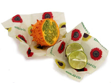 Load image into Gallery viewer, Sustainable Vegan Wax wrap 2 Mini 2 Small in action, covering the cut sides of tropical fruit and limes as an eco-friendly alternative to plastic wrap. All wraps are in the print Among the Sunflowers, which is a cheerful collection of traditional yellow and brilliant red sunflowers accompanied by the Khala & CO logo in green.
